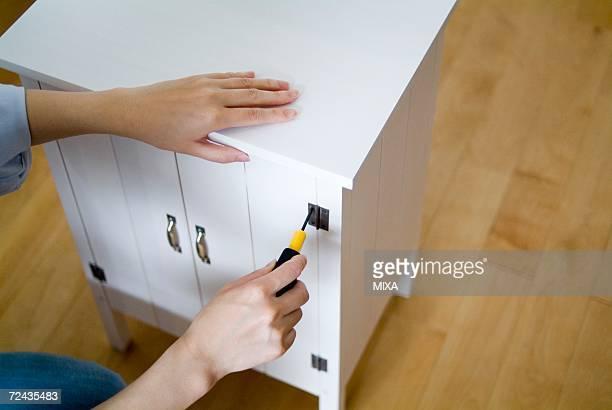 a woman assembling dresser - 引き出し ストックフォトと画像