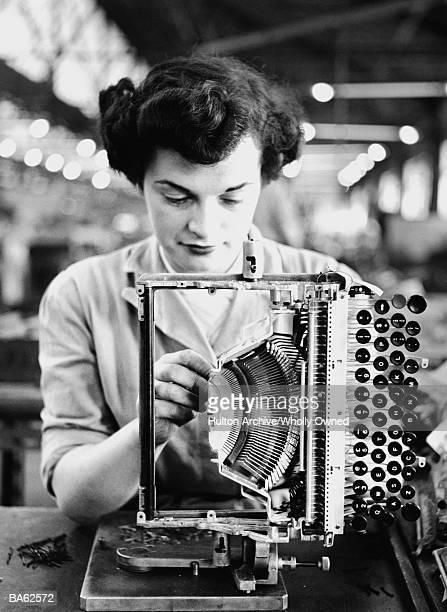 Woman assembling typewriter in factory (B&W)