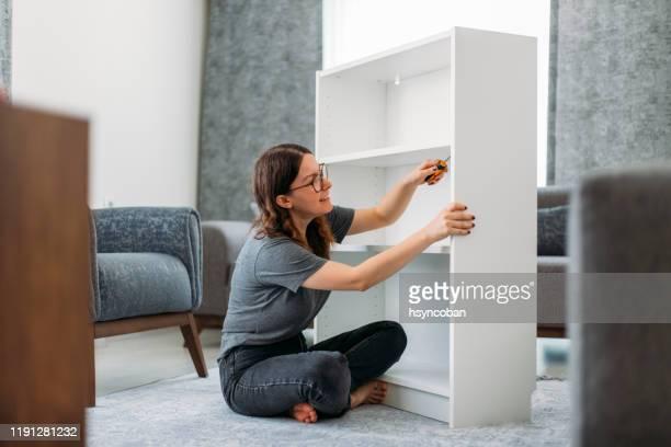 donna che assembla armadio di legno in casa - mobilio foto e immagini stock