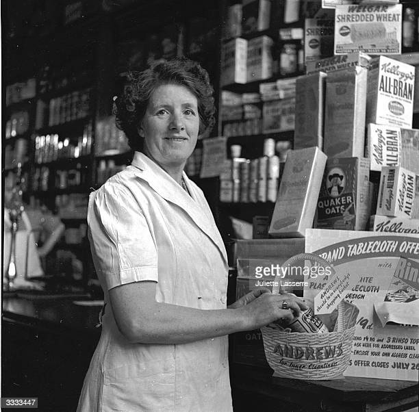 A woman assistant in a grocery shop on the Isle of Man arranging a counter display consisting of cornflakes and porage oats plus a basket of health...