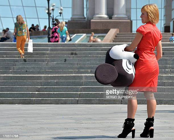 A woman assistant of a street photographer carries the mask of a cartoon characters in spite of hot temperatures as she walks looking for clients in...