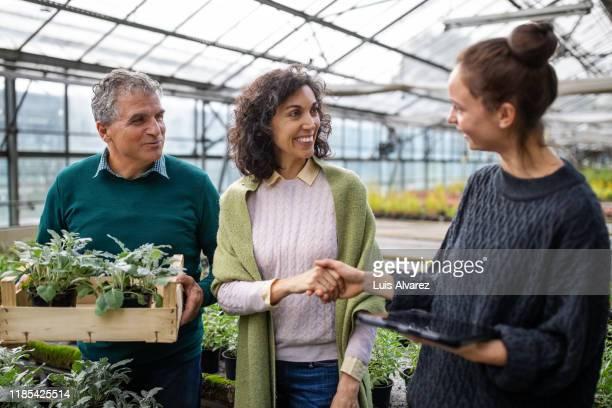 woman assisting customer at garden center - teil einer serie stock-fotos und bilder