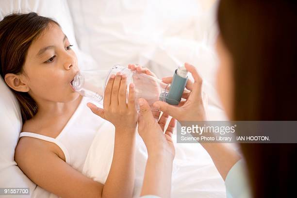 Woman assisting girl with asthma inhaler