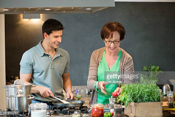 Woman assisting her son to cook food in the kitchen