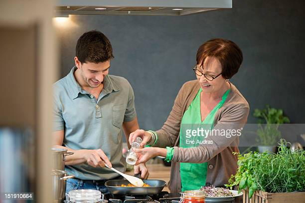 Woman assisting her son to cook food
