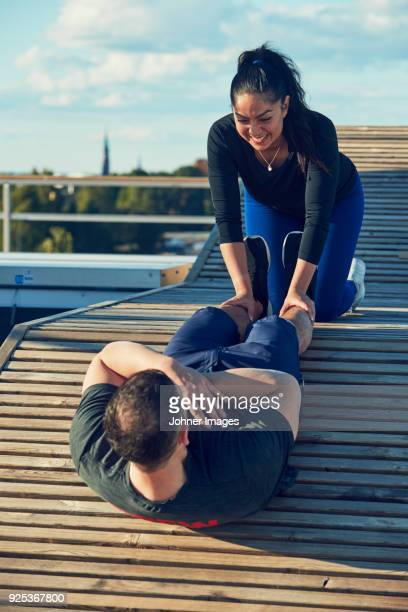 woman assisting man in doing sit-ups - all weather running track stock pictures, royalty-free photos & images