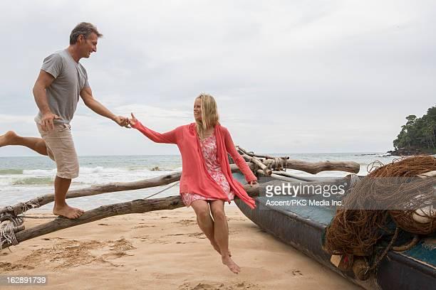 Woman assists man balancing along boat pontoon