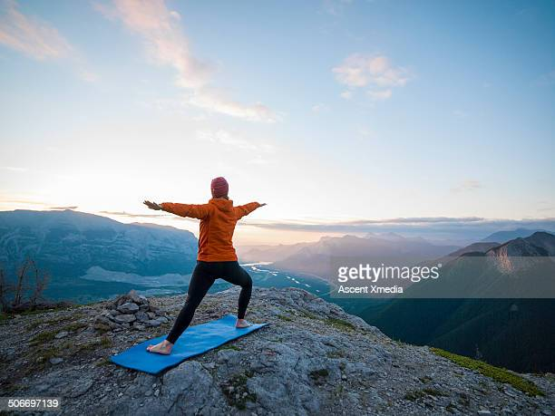 Woman assumes yoga position on high mtn crest