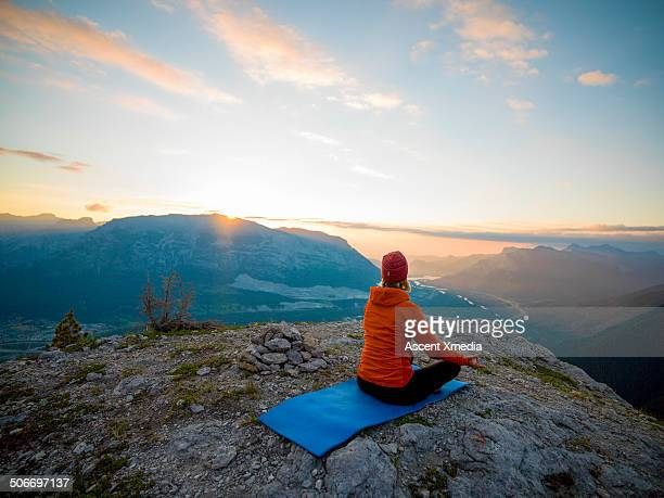 Woman assumes yoga stance on high mtn crest