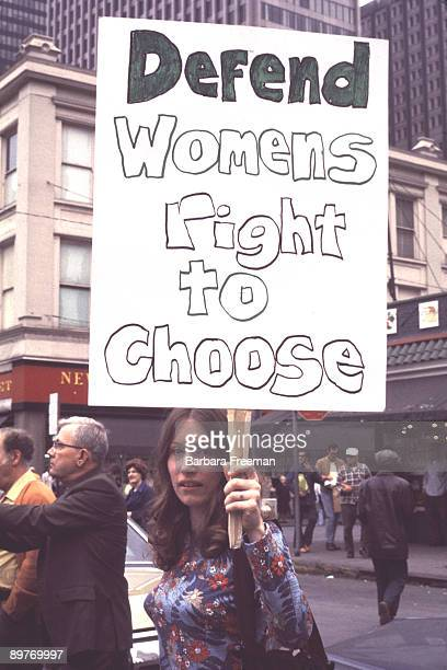 A woman at a 1974 reproductive rights march in Pittsburgh PA holds a sign reading 'Defend Womens Right To Choose'