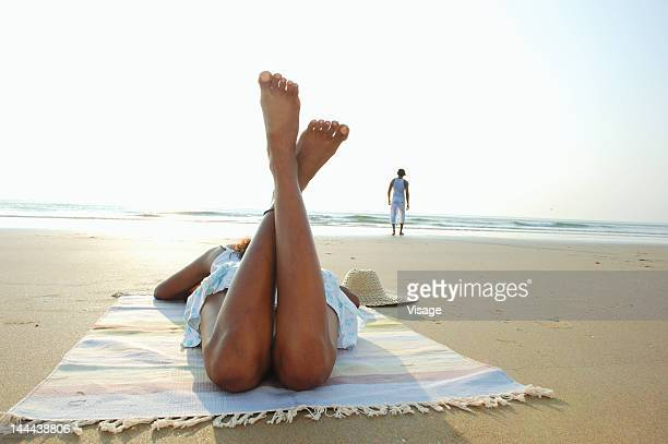 A woman at a beach with her legs crossed