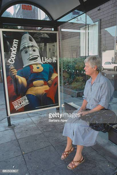 A woman at a bus stop in San Francisco California next to an AIDSawareness poster advocating the use of condoms October 1989