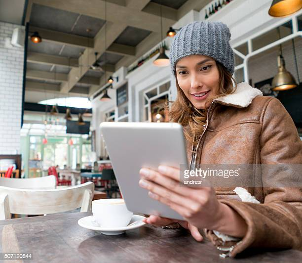 Woman at a cafe reading on a tablet