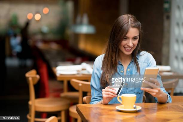 Woman at a cafe shopping online