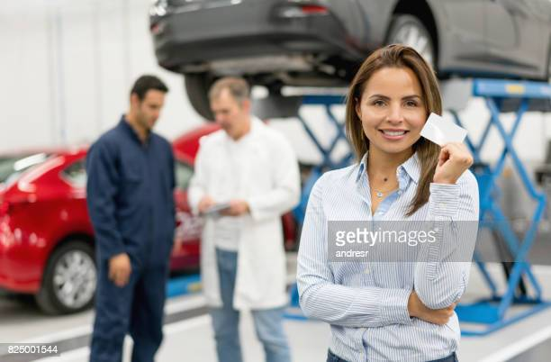 Woman at a car garage holding a business card