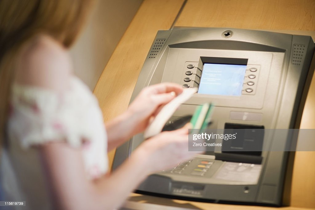 Woman at a cashpoint : Stock Photo