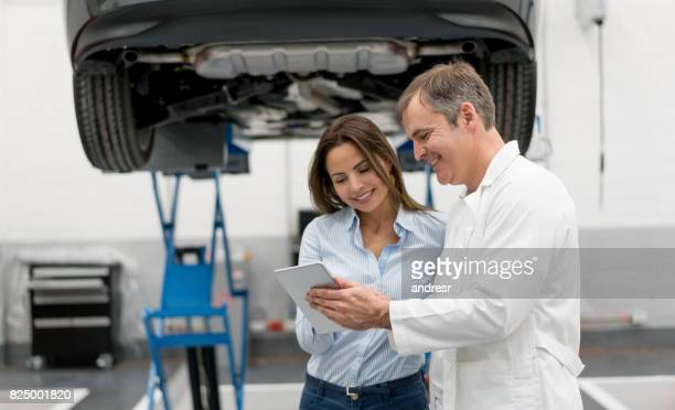 Woman at a garage talking to a mechanic fixing her car