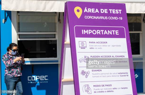 Woman at a gas station waits for her turn for a COVID-19 coronavirus test, in Santiago, on May 13, 2020. - Chile's government ordered a mandatory...