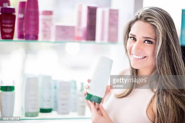 Mulher em um salão de cabeleireiro Segurando os produtos de beleza