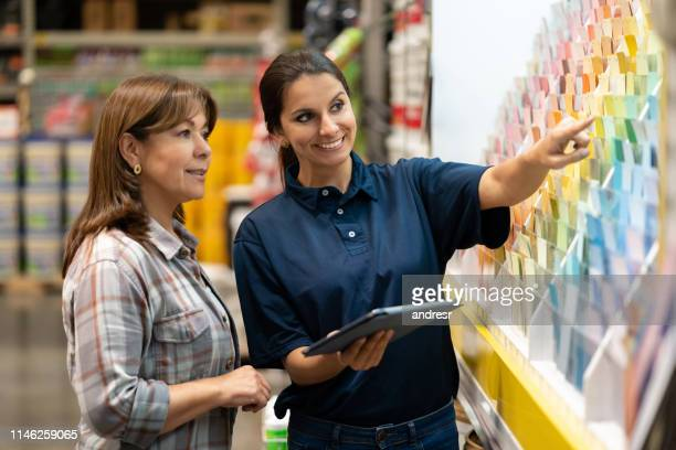 woman at a home improvement store choosing paint colors - assistant stock pictures, royalty-free photos & images