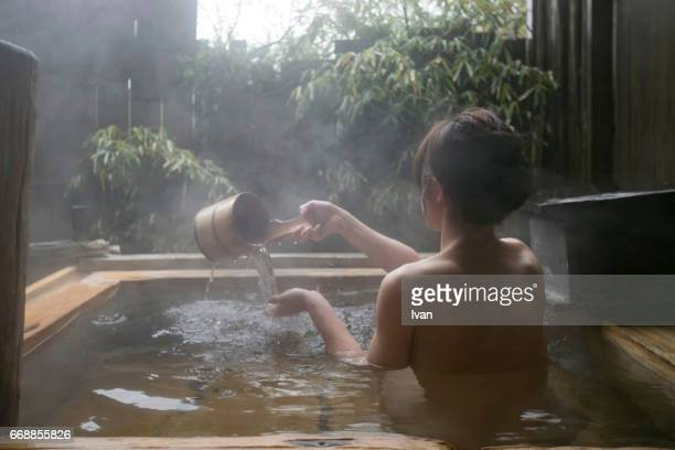 Woman at a Japanese Style Spa Resort in a Hot Spring Pool