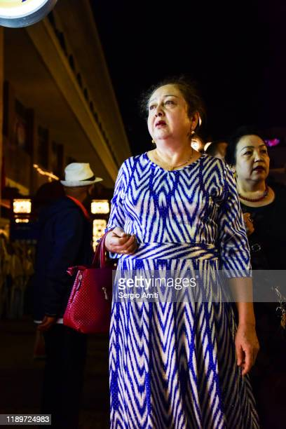 woman at a night market in urumqi - sergio amiti stock pictures, royalty-free photos & images