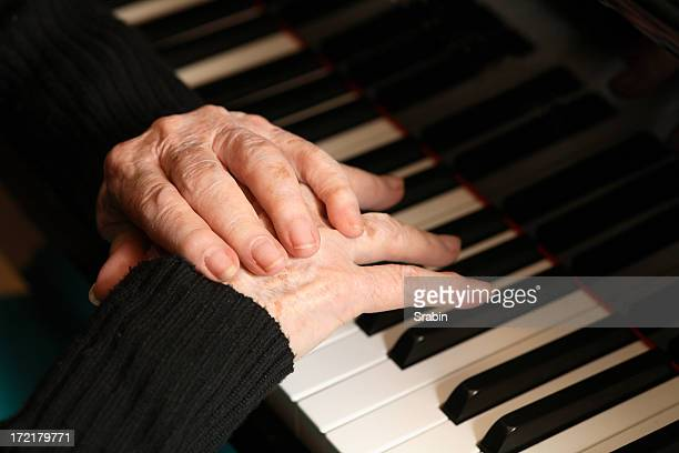 Woman at a piano rubbing her pained hands