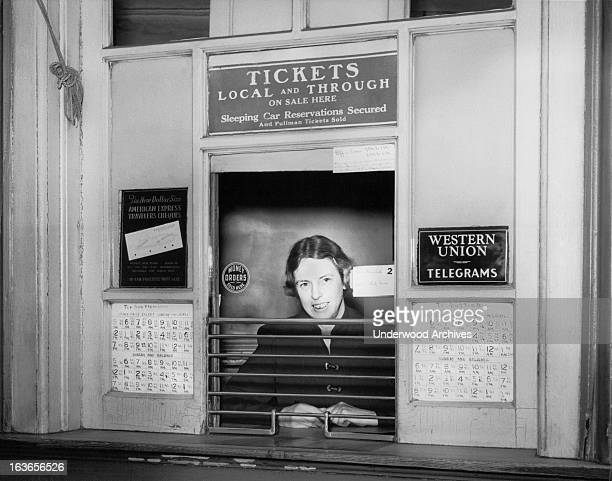 A woman at a railroad ticket counter selling tickets to San Francisco and Dutton Avenue in San Leandro along with American Express Traveler's Cheques...