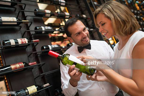 Woman at a wine cellar talking to the sommelier