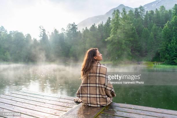 woman at alpine lake, engadin, switzerland. - solo adulti foto e immagini stock