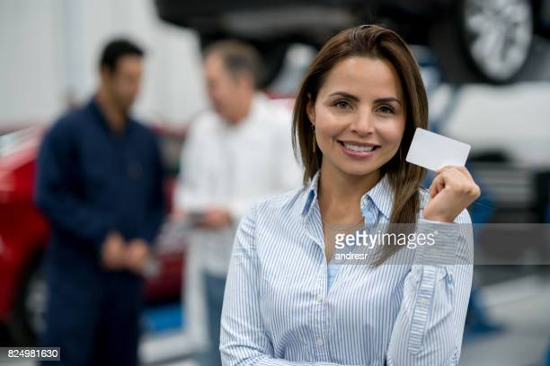 Woman at an auto repair shop holding a business card