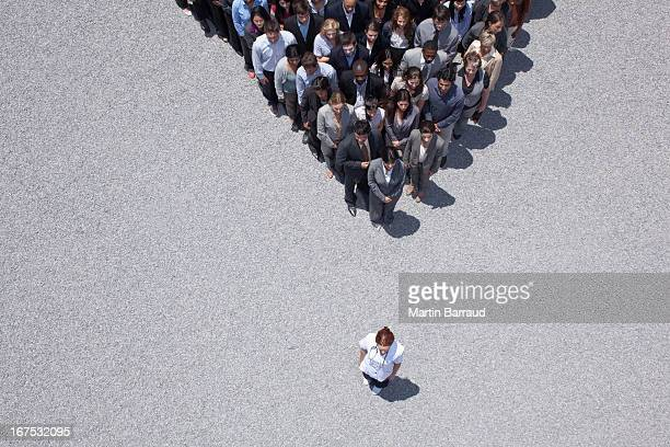 woman at apex of crowd - following stock pictures, royalty-free photos & images
