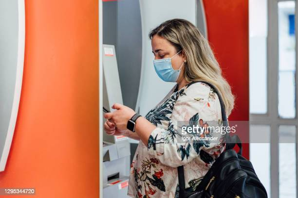 woman at bank atm - chubby credit stock pictures, royalty-free photos & images