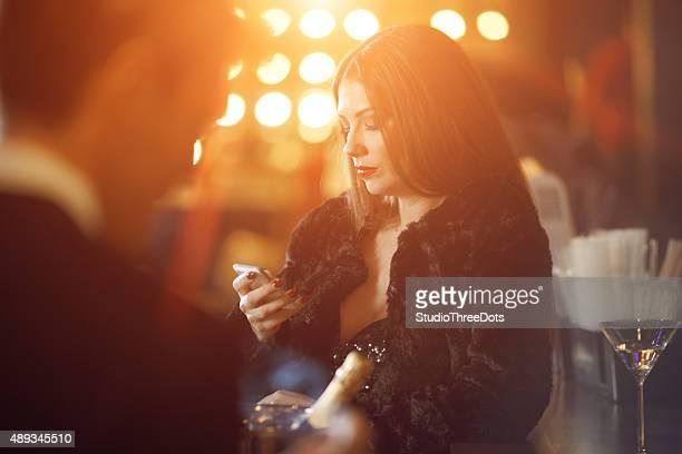 Woman at bar looking at cell phone