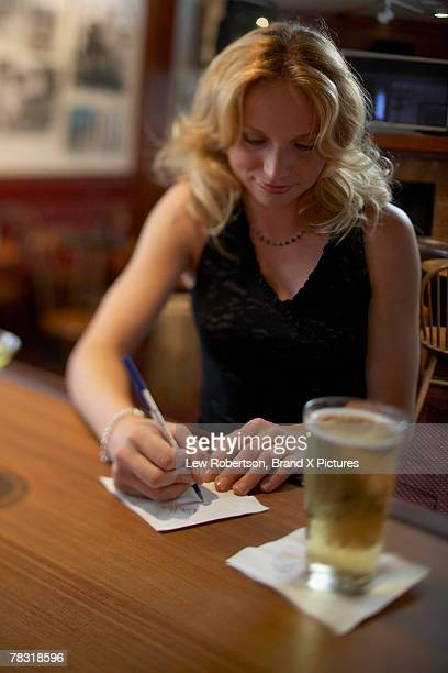 woman at bar writing on napkin - telephone number stock pictures, royalty-free photos & images