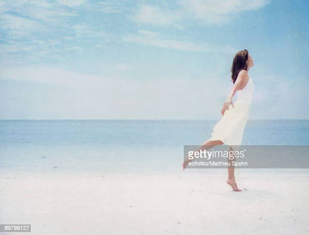 Woman at beach, balancing on one leg