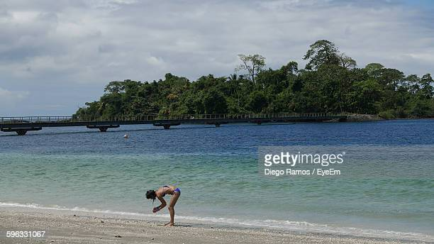 Woman At Beach By Bridge Against Mountains
