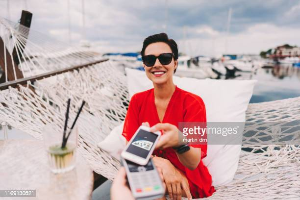 woman at beach cafe paying contactless - financial technology stock pictures, royalty-free photos & images