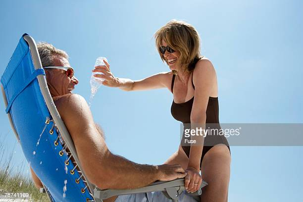 Woman at Beach Pouring Water on Man s Chest