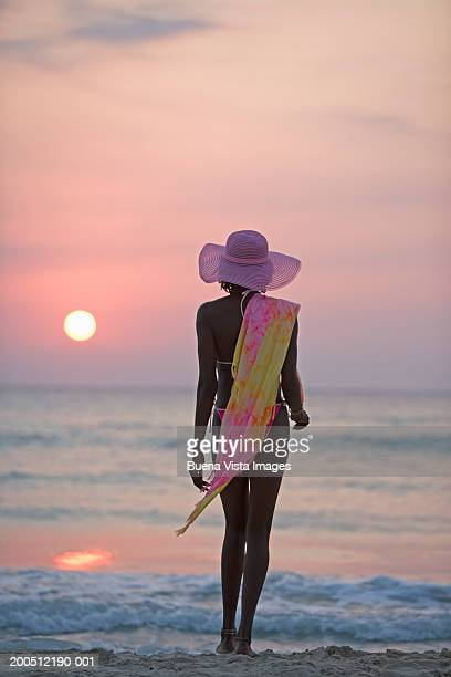 Woman at beach, sunset, rear view
