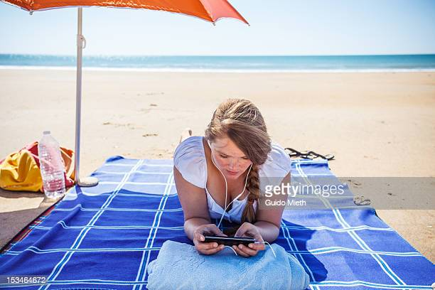 Woman at beach with mobile phone.