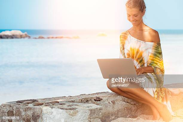 Woman at beach working on laptop