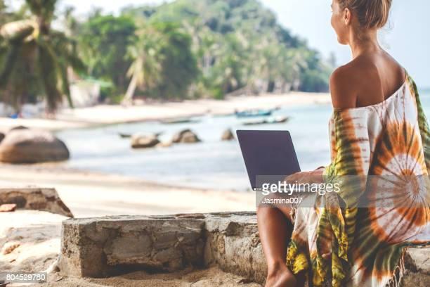 Vrouw aan het strand die op laptop werkt