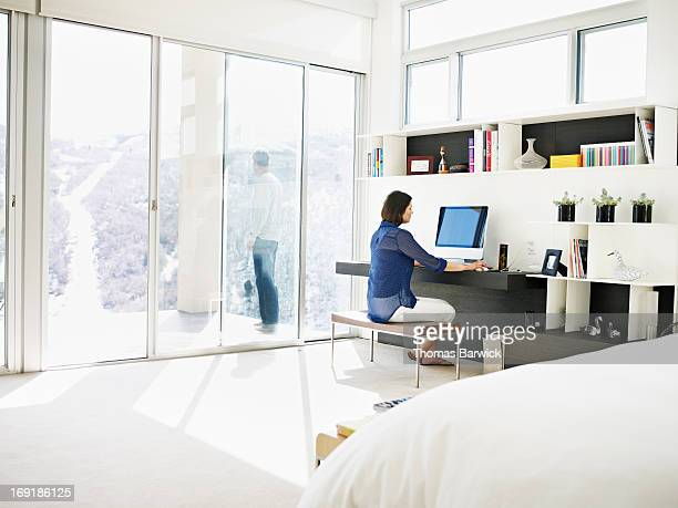 Woman at bedroom desk with husband in background
