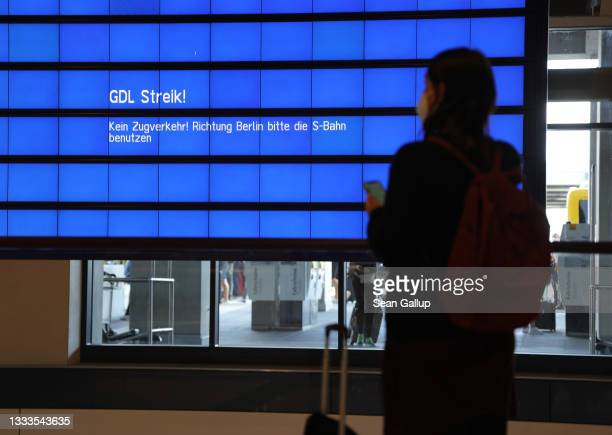 Woman at Berlin Brandenburg Airport looks toward a train departures screen warning of a strike by the GDL labor union during a nationwide railway...