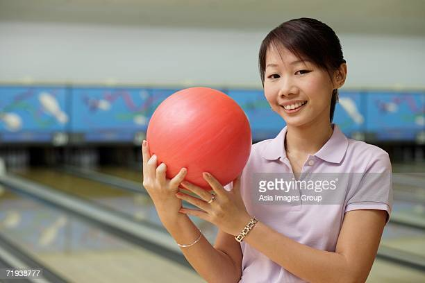 woman at bowling alley, smiling, holding bowling ball - ポロ ストックフォトと画像
