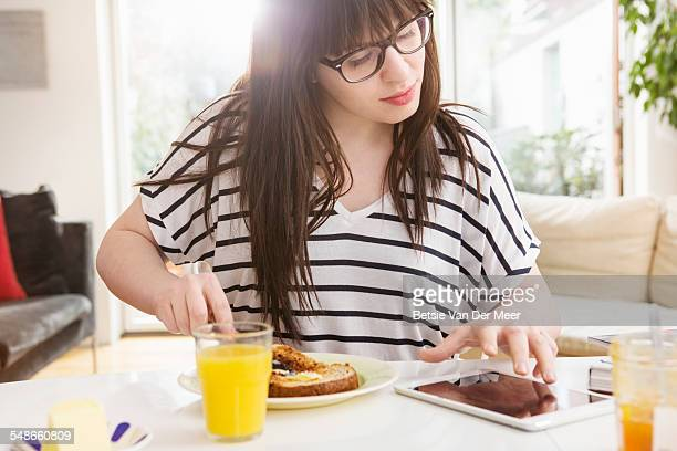 Woman at breakfast table checks digital tablet.