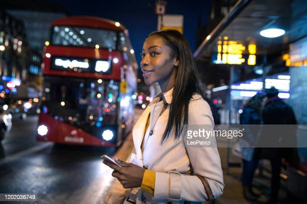 woman at bus stop in the night in london - waiting stock pictures, royalty-free photos & images