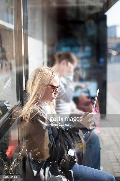 woman at bus stop looking at tablet - newtechnology stock pictures, royalty-free photos & images