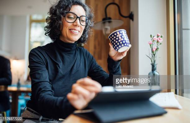 woman at cafe using digital tablet at coffee shop - tablet benutzen stock-fotos und bilder